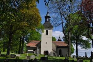 Julita kyrka ligger vackert inbäddad i grönskan vid sjön Öljaren Södermanland